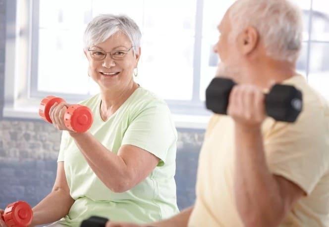 Пожилые люди делают упражнения для тренировки сердца